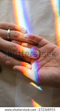 hand in hand with rainbow - stock photo