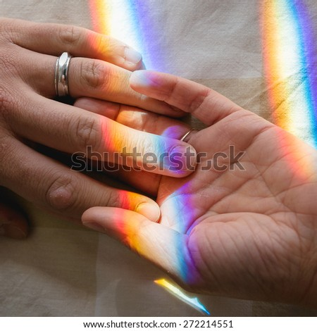 hand in hand with rainbow as a bond - stock photo