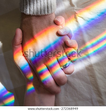 hand in hand with rainbow symbolizing eternal love - stock photo
