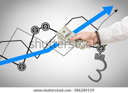 Hand in handcuffs holding money. Graphs at background. Concept of financial crime. - stock photo