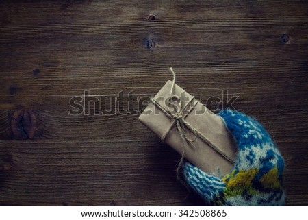 Hand in knitted mittens holding present, rustic wood background, top view, copy space, toned
