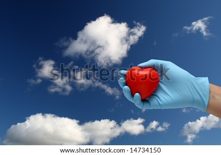 hand in latex blue gloves holding a toy heart under a blue sky