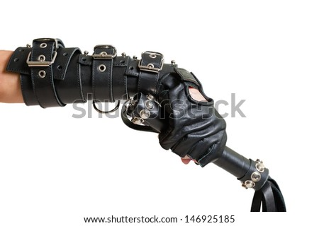 Hand in leather glove with lash - stock photo