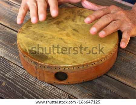 hand in motion of senior man playing ethnic drum - stock photo