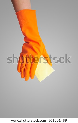 Hand in orange rubber glove with sponge isolated on gray background. cleaning - stock photo