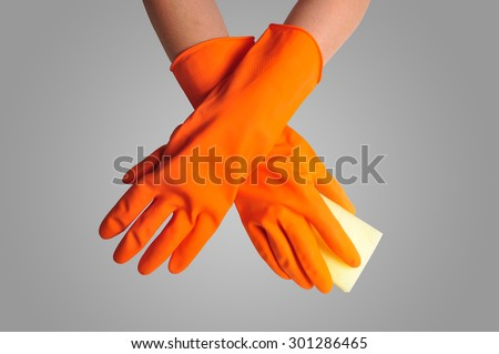 Hand in orange rubber glove with sponge isolated on gray color background. cleaning - stock photo