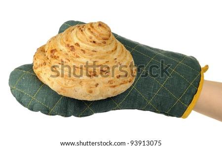 Hand in Oven Mitt Holding Freshly Baked Bun on White Background - stock photo