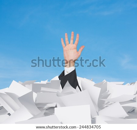 hand in papers heap on a sky background - stock photo