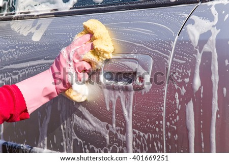 Hand in pink protective glove washing a silver car with sponge. Early spring washing or regular wash up. Professional car wash by hands. - stock photo