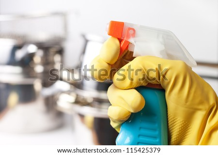 hand in protective glove holding spray. cleaning a kitchen concept - stock photo