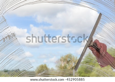 Hand in protective glove washing and cleaning window with bigger professionally squeegee on background of cloudy sky. Summer windows cleaning. Maid cleans window. - stock photo
