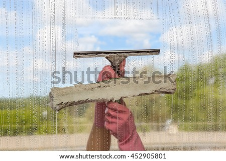Hand in protective glove washing and cleaning window with professionally mop and squeegee on background of cloudy sky. Summer windows cleaning. Maid cleans window. - stock photo