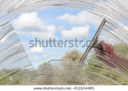 Hand in protective glove washing and cleaning window with professionally squeegee on background of cloudy sky. Summer windows cleaning. Maid cleans window. - stock photo