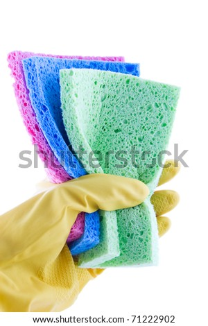 Hand in rubber glove holding colorful sponges on white