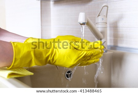 Hand in rubber glove in water stream at kitchen faucet