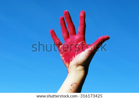 hand in the paint against the sky - stock photo