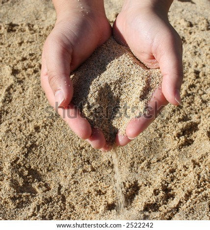 hand in the shape of a heart dropping sand