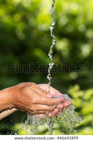 hand in the water in nature - stock photo