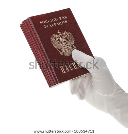 Hand in white glove holding a stack of Russian passports - stock photo
