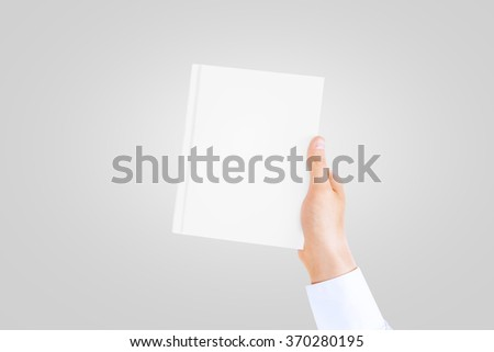 Hand in white shirt sleeve holding closed blank book cover mock up in the hand. Book front holding in sleeve shirt hand. Vertical catalogue template mock up hold in arm. Clear notebook cover.