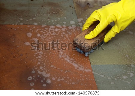 Hand in yellow glove cleaning dirty filthy floor with brush indoors - stock photo