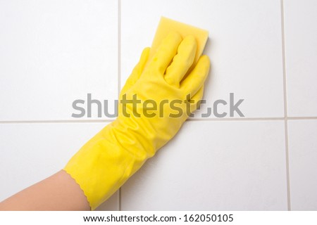 Hand in yellow glove cleaning tile wall - stock photo