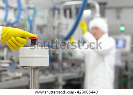 hand in yellow  glove pressing button - starting industrial process - stock photo