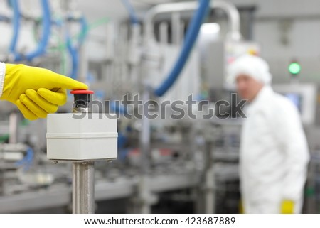 hand in yellow  glove pressing button - starting industrial process