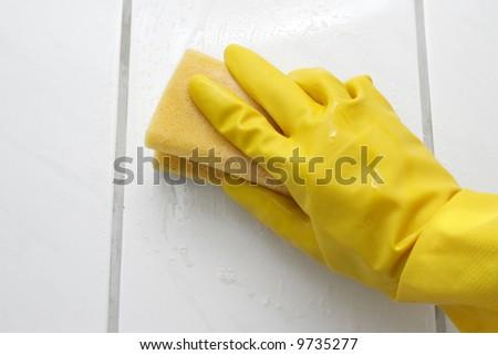 Hand in yellow glove with sponge, washing bathroom's wall - stock photo