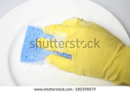 Hand in yellow latex glove cleaning white plate with blue sponge