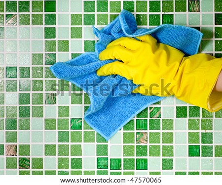 Hand in yellow protective glove  cleaning mosaic wall - stock photo
