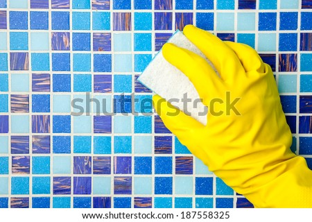 Hand in yellow protective glove cleaning mosaic wall with sponge - stock photo