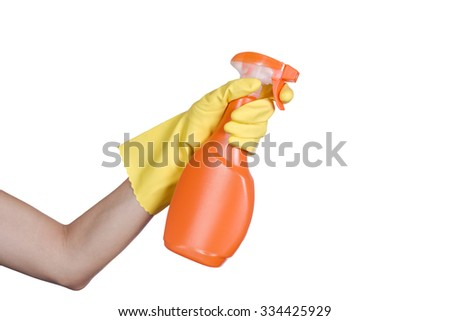 Hand in yellow protective glove spraying cleaning liquid on white background - stock photo