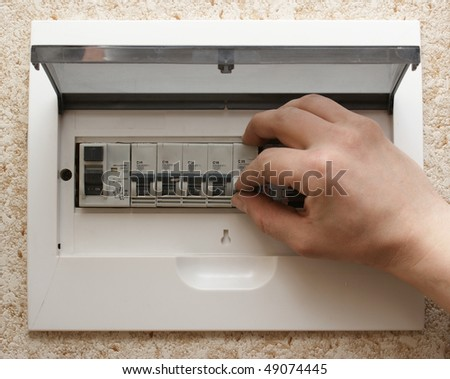 Hand including the switch on the electric panel