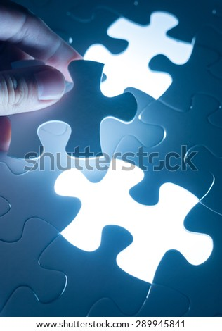 Hand insert jigsaw, conceptual image of business strategy, decision making concept