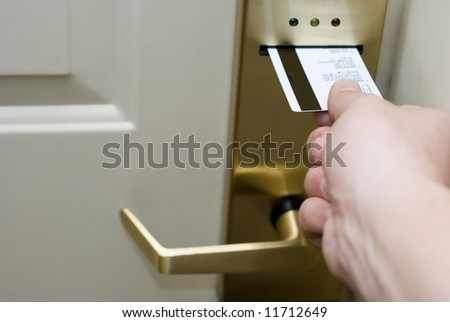 Hand inserting a keycard into a hotel electronic hotel door lock