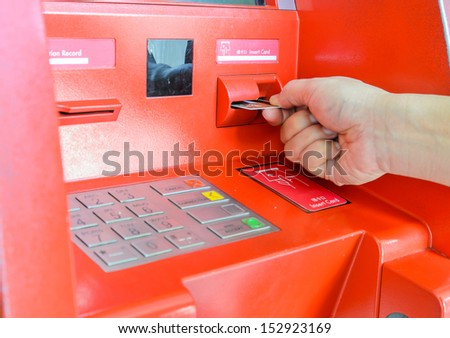 Hand inserting ATM card in ATM machine - stock photo