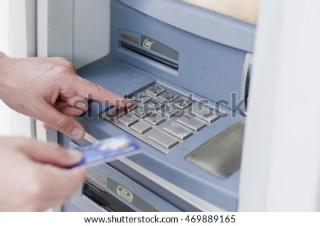 Hand inserting ATM card into bank machine to withdraw money. businessman men hand puts credit card into ATM