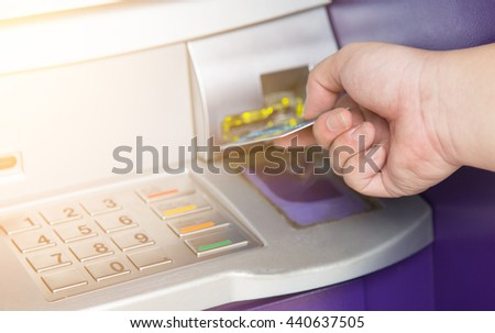 Hand inserting ATM credit card into bank machine - stock photo