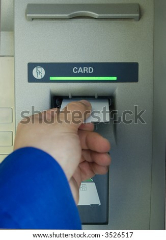 hand inserting blank card into cash machine - stock photo
