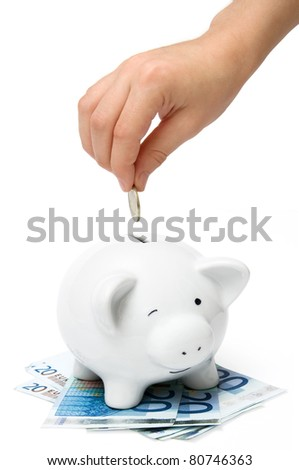 Hand inserting coin into piggybank isolated on white background - stock photo