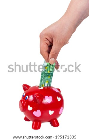 Hand inserting 100 euro banknote into piggy bank isolated on white background with clipping path - stock photo