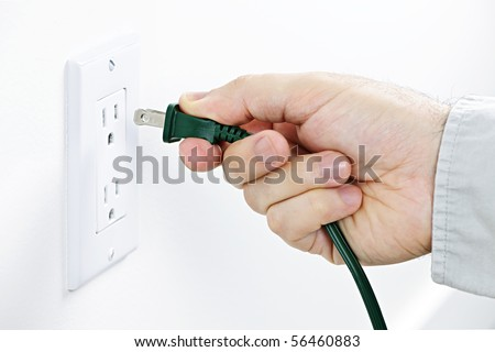Hand inserting green electrical plug into outlet - stock photo