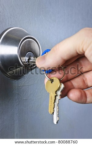 Hand inserting keys in door lock close up - stock photo