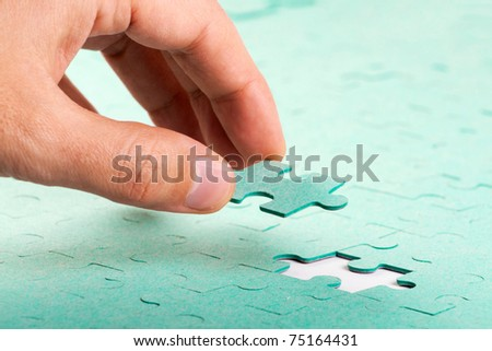 Hand inserting missing piece of green jigsaw puzzle into the hole - stock photo