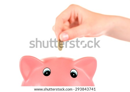Hand inserting money into piggy bank isolated on white