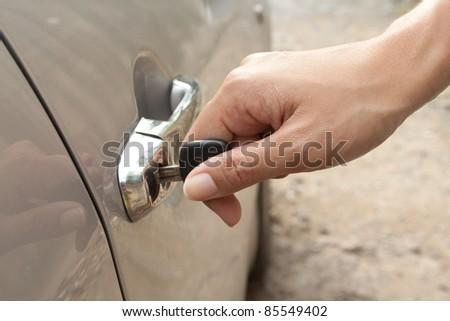 Hand inserting the car's key - stock photo