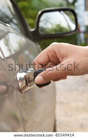 Hand inserting the car's key - stock photo