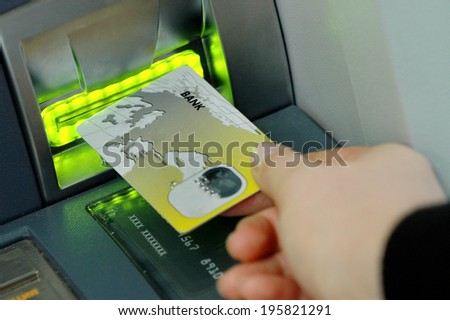hand inserts the card into the ATM - stock photo