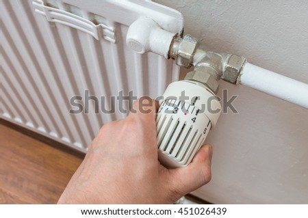 Hand is adjusting temperature of radiator. Heating concept.